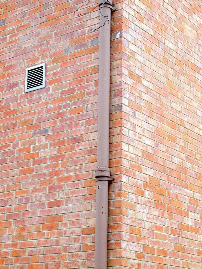 Tubo dell'impianto idraulico contro la parete dello stucco immagine stock
