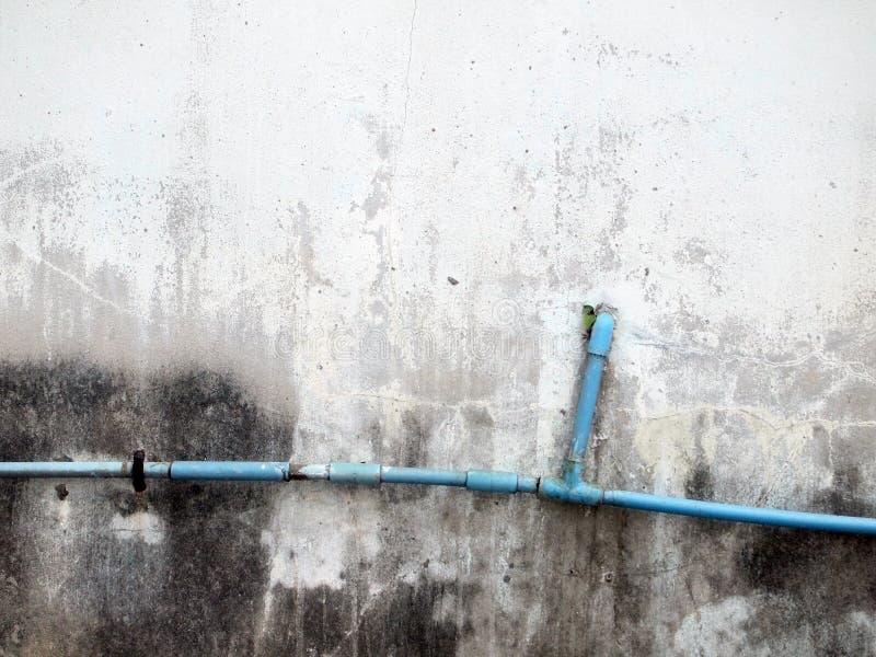 Tubo dell'impianto idraulico contro la parete dello stucco fotografie stock