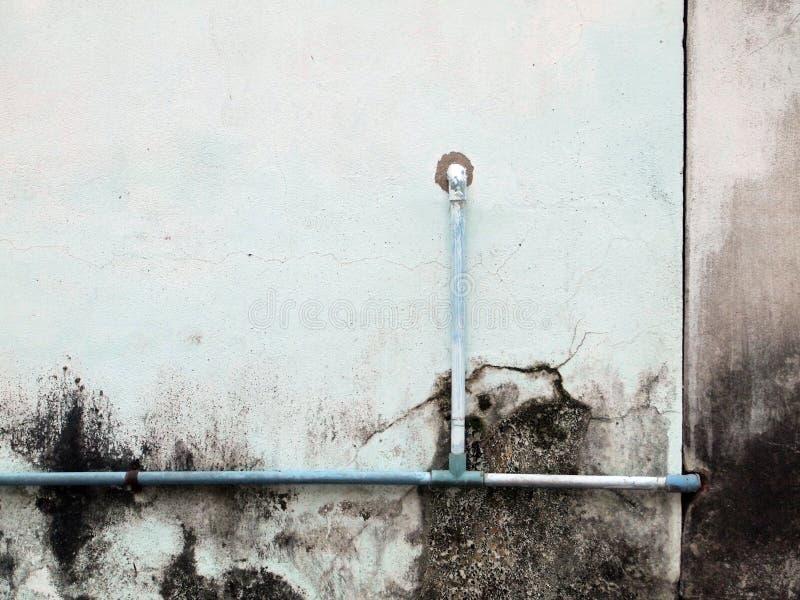 Tubo dell'impianto idraulico contro la parete dello stucco fotografia stock