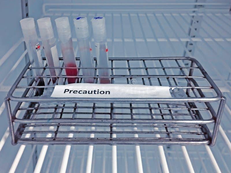 Tubo della raccolta del sangue del campione con l'etichetta di precauzione sullo scaffale immagine stock