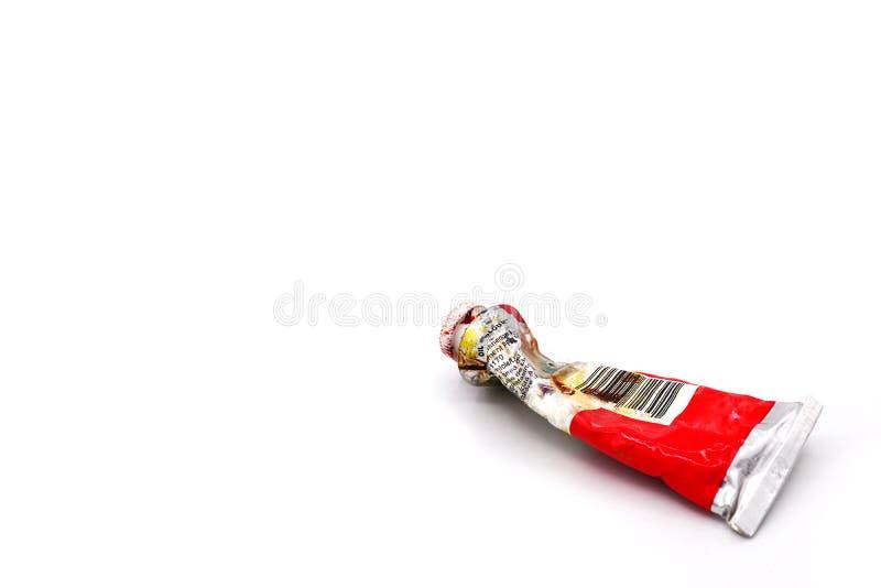 Tubo di colore a olio rosso utilizzato schiacciato secco chiuso-su per la verniciatura su un fondo bianco tubo di olio unico orig immagine stock