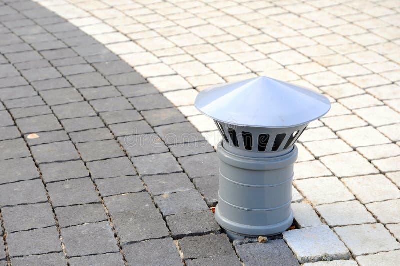 Tubo di plastica per lo scarico che esce dalla terra Lastre per pavimentazione con il closee di sporgenza del tubo su immagine stock