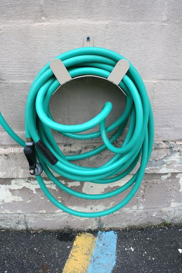 Tubo flessibile arrotolato verde Hung On Cement Wall fotografia stock