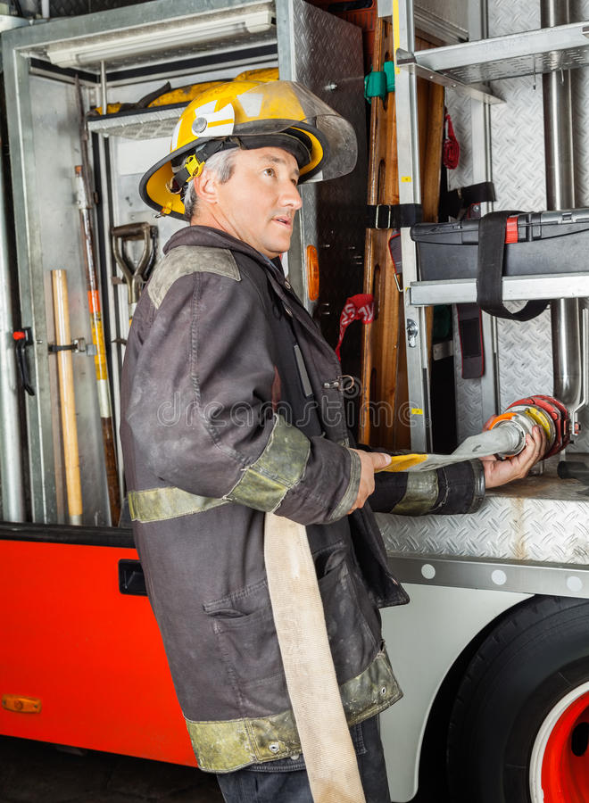 Tubo flessibile dell'acqua della riparazione del vigile del fuoco in camion alla caserma dei pompieri fotografie stock libere da diritti