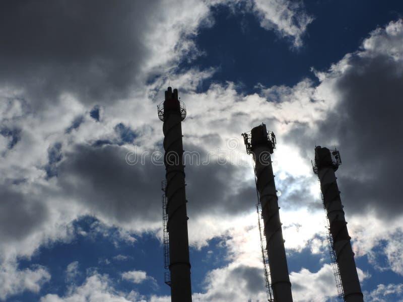 Tubo industriale vecchio del mattone rosso e bianco sul fondo del cielo blu La vecchia immagine del concetto di industria Ecologi fotografia stock libera da diritti