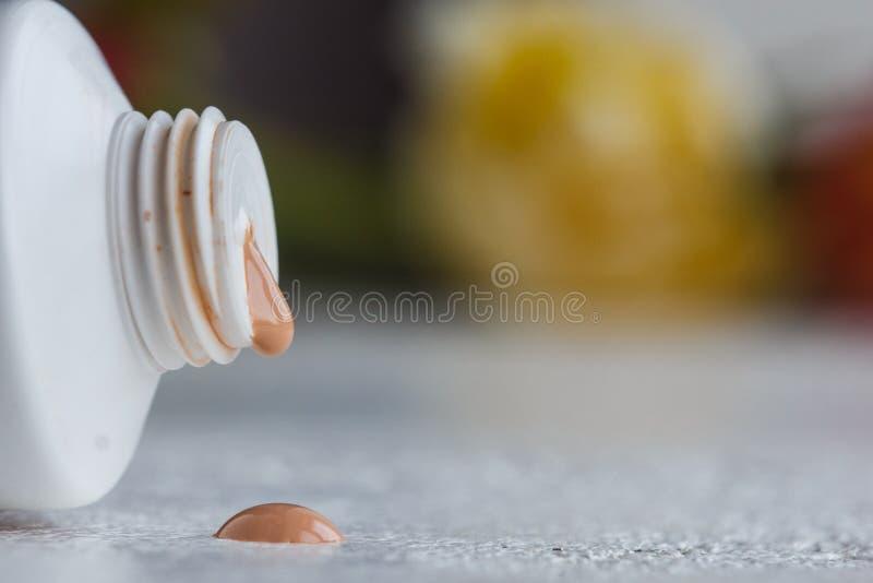 Tubo pl?stico da boca com creme e close-up aberto da tampa em uma tabela branca cosm?ticos para o close-up do cuidado do corpo em foto de stock