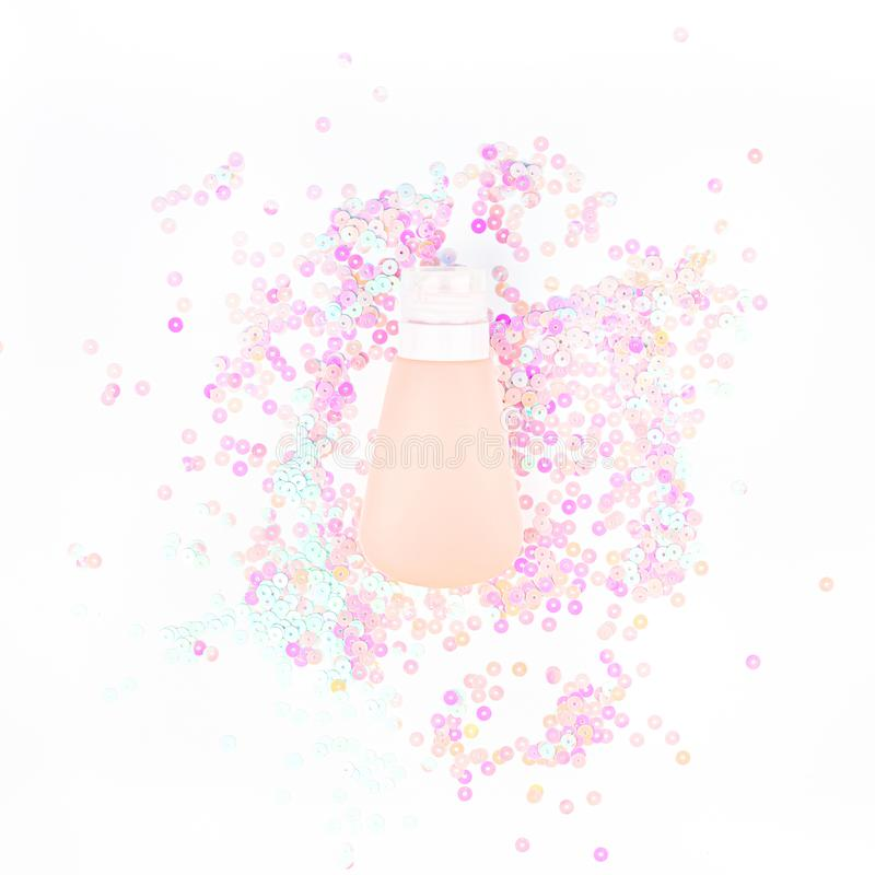 Tubo poner crema cosm?tico en confeti en colores pastel de la perla imagenes de archivo