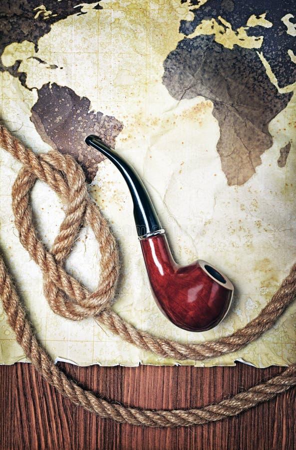 Tubo que fuma del vintage y nudo de la cuerda con el mapa viejo en el papel manchado retro amarillo imagen de archivo
