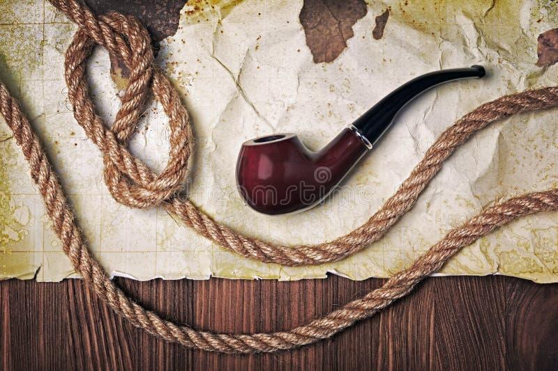 Tubo que fuma del vintage y nudo de la cuerda con el mapa viejo en el papel manchado retro amarillo fotografía de archivo libre de regalías
