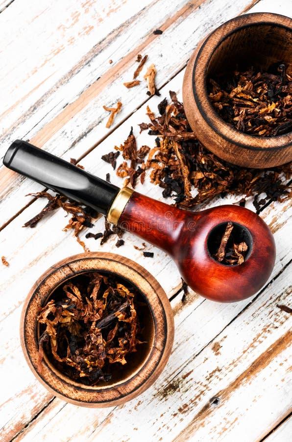 Tubo que fuma en una tabla de madera fotografía de archivo