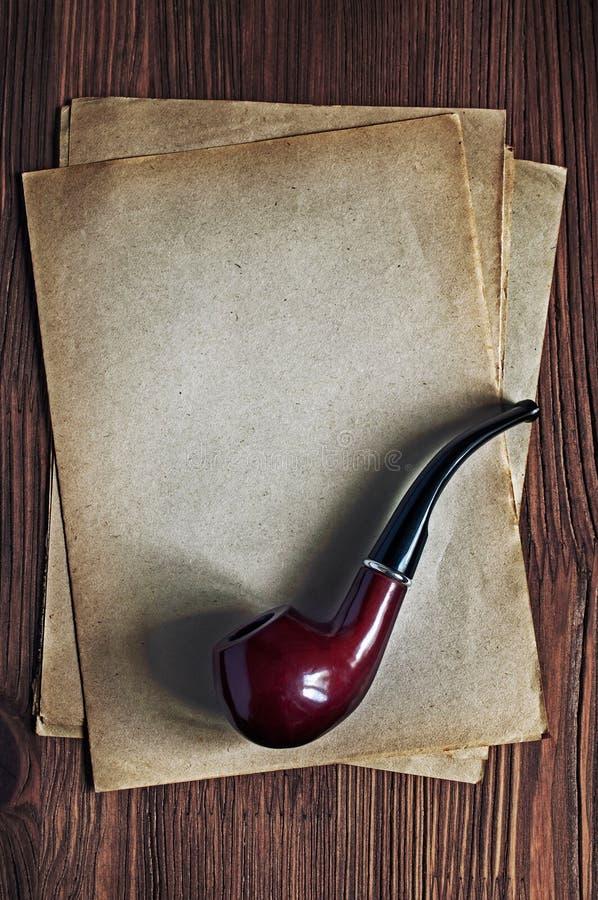 Tubo que fuma y hoja de papel amarilleada vieja imagen de archivo