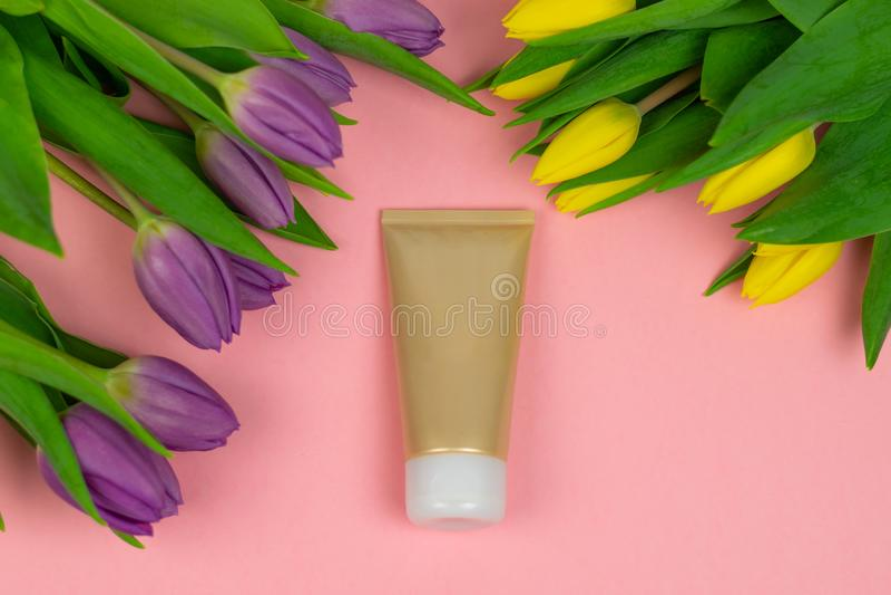 Tubo vac?o de la crema en un fondo rosado con las flores imagenes de archivo
