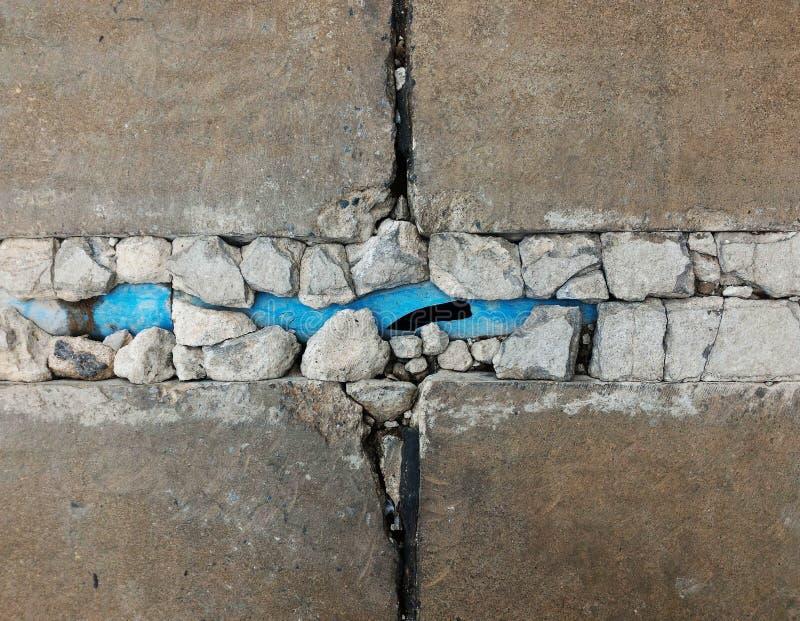 Tubo viejo quebrado del pvc del azul bajo vieja tierra concreta quebrada fotografía de archivo
