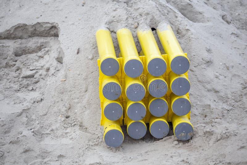 Tubos amarillos del PVC para los sistemas de cable enterrados en la arena fotos de archivo