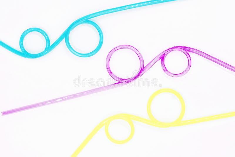 Tubos coloreados para los cócteles maravillosamente formados, primer en un fondo blanco imagen de archivo libre de regalías