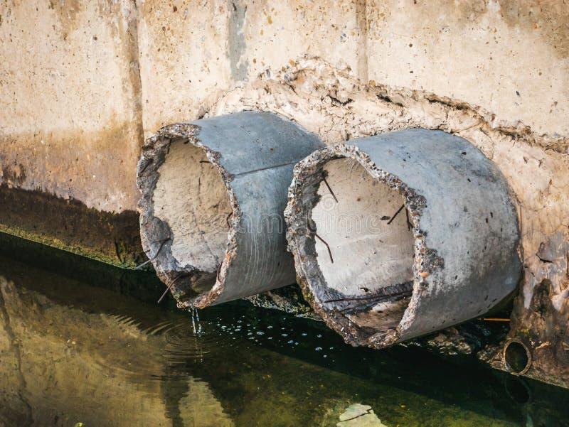 Tubos concretos del drenaje o del alcantarillado, agua sucia y contaminación del ambiente fotos de archivo