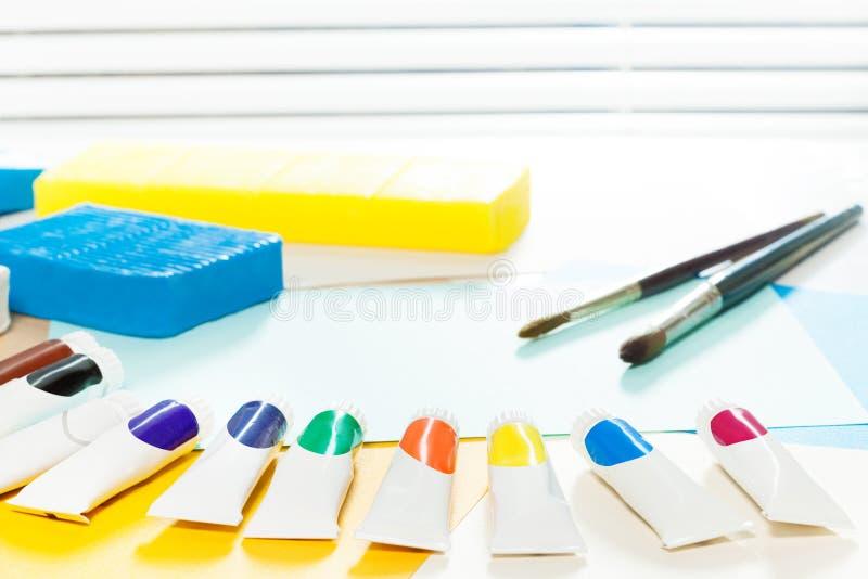 Tubos da pintura que colocam em uma tabela durante a lição da arte foto de stock royalty free