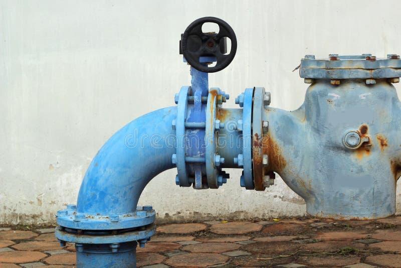 Tubos de agua industriales del metal oxidado azul con una válvula fotos de archivo