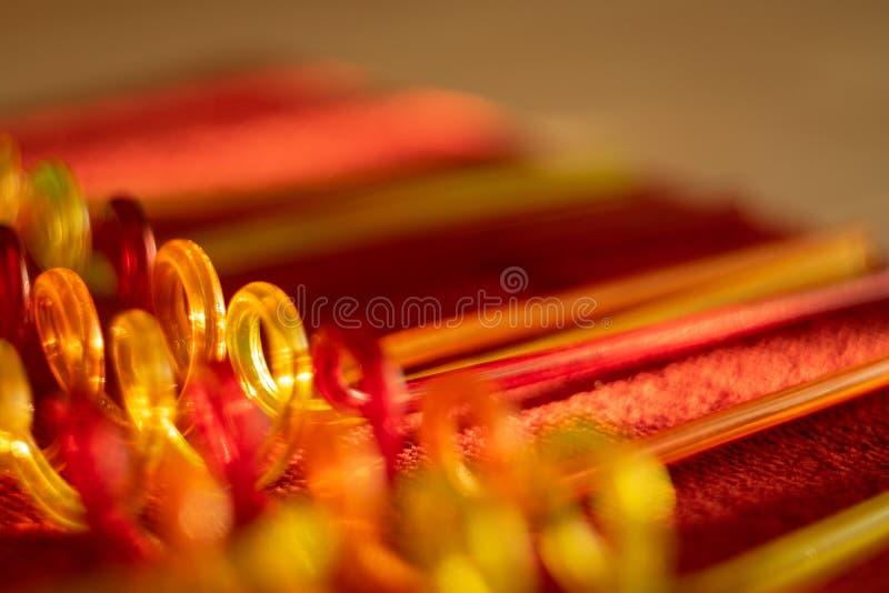 Tubos de color para los jugos de consumición El fondo brillante borroso transmite la atmósfera festiva fotografía de archivo