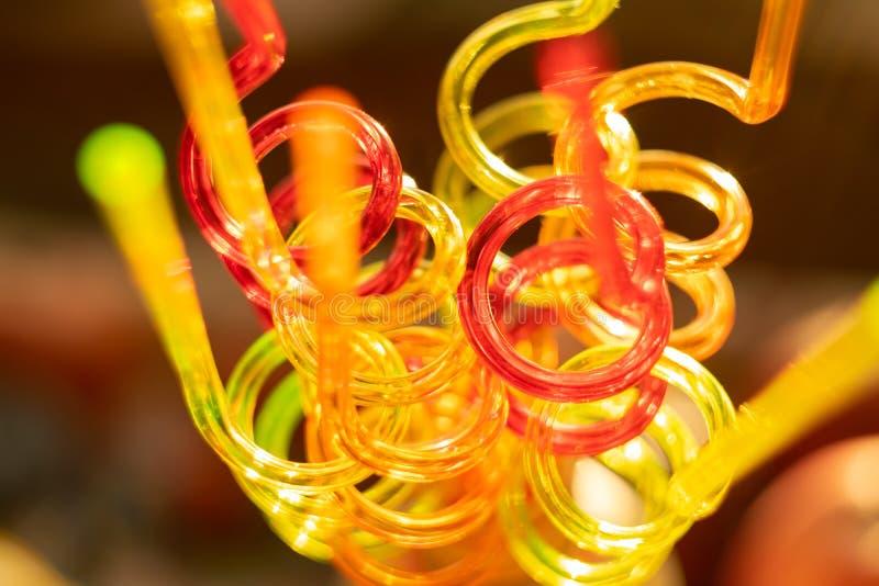 Tubos de color para los jugos de consumición en un fondo del color El fondo brillante borroso transmite la atmósfera festiva foto de archivo libre de regalías