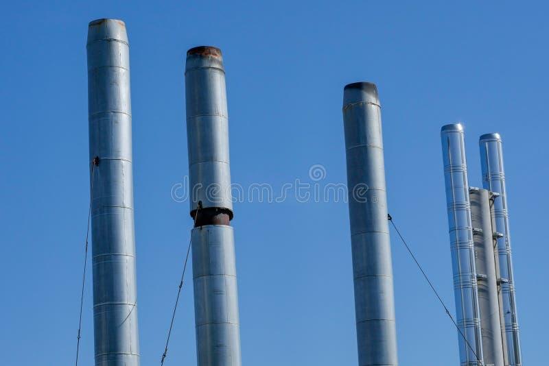 Tubos de cuartos de caldera de gas en el fondo del cielo azul del verano El humo de los tubos no va fotos de archivo