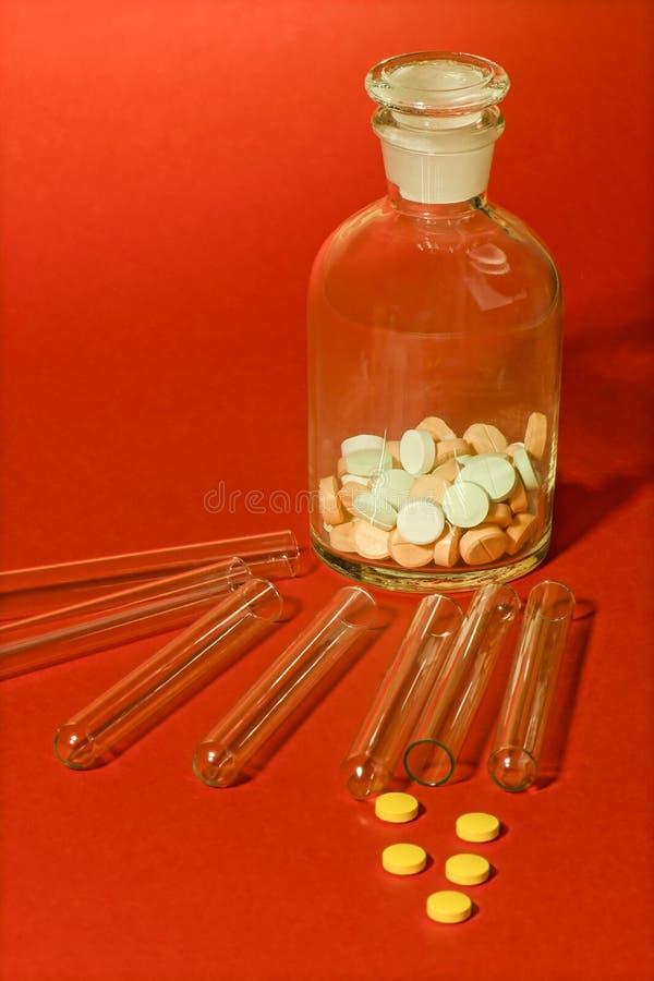 Tubos de ensaio com o recipiente e as tabuletas de vidro da medicina imagens de stock