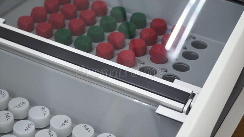 Tubos de ensaio e garrafas arranjados no trole médico grampo Cremalheira dos tubos de ensaio no laboratório médico Análise labora foto de stock