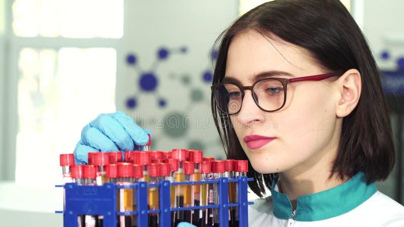 Tubos de ensaio de exame do pesquisador fêmea novo com amostras de sangue fotos de stock royalty free