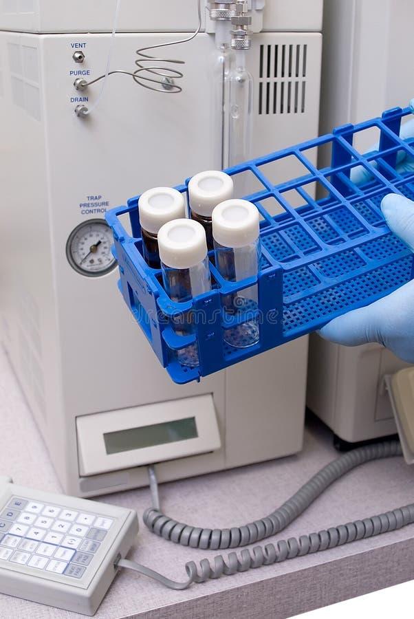 Tubos de ensaio, frascos e tampões do laboratório em uma cremalheira fotografia de stock