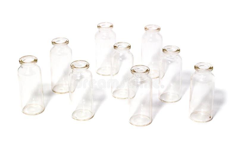 Tubos de ensaio de vidro em uns produtos vidreiros de laboratório brancos do fundo fotografia de stock