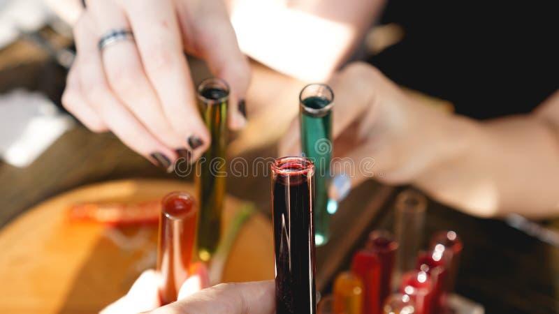 Tubos de ensayo con el l?quido multicolor Alcohol en barra oscura de los tubos de ensayo imágenes de archivo libres de regalías