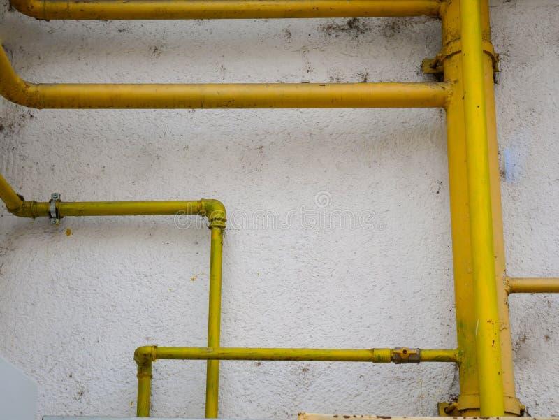 Tubos de gas amarillos en la pared constructiva sucia vieja imagenes de archivo