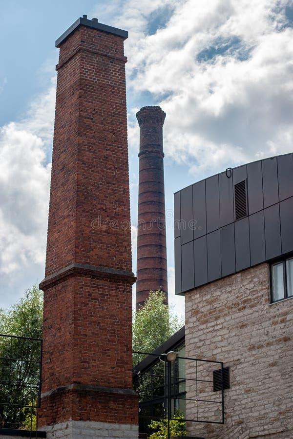 Tubos de tijolos altos do crematório contra o céu com nuvens imagem de stock royalty free
