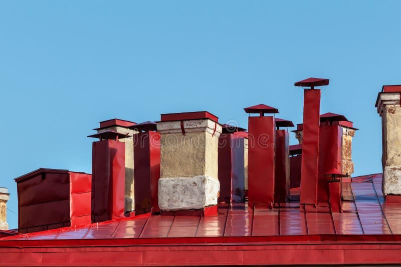 Tubos del horno y de la ventilación en el tejado rojo imagen de archivo