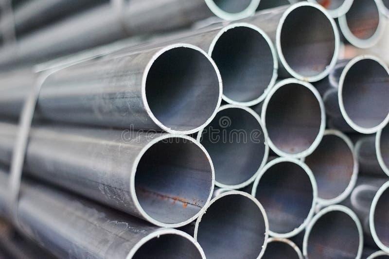 Tubos del metal en un almacén Pilas de nueva tubería de acero redonda foto de archivo