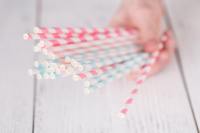 Tubos disponibles del papel rayado en una mano de la mujer imágenes de archivo libres de regalías