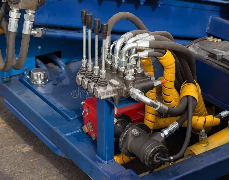 Tubos, encaixes e alavancas hidráulicos no painel de controle foto de stock