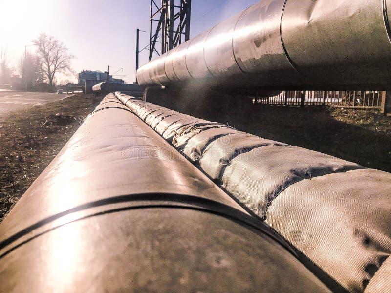 Tubos gruesos grandes del metal para los líquidos de bombeo, agua, vapor, aceite, gas licuado en el aislamiento térmico hecho de  fotografía de archivo