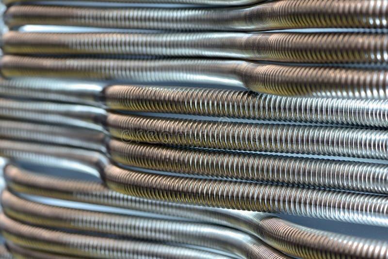 Tubos inoxid?veis ondulados do metal para a fonte de ?gua Fundo industrial abstrato foto de stock