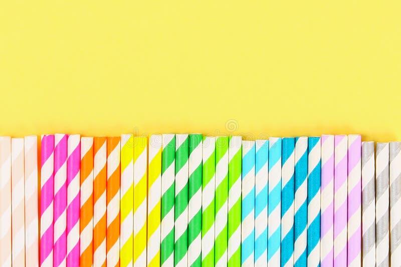 tubos Multi-coloridos do papel de palha em um fundo pastel amarelo brilhante Vista superior, espaço da cópia fotografia de stock
