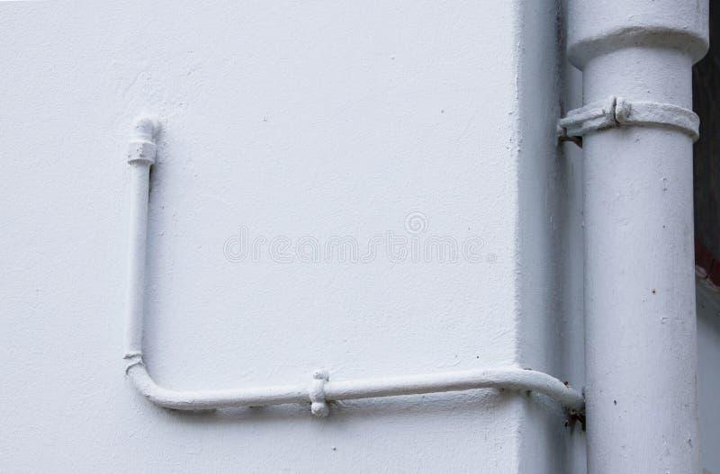 Tubos pintados de la fontanería del metal en Pale Blue Wall foto de archivo libre de regalías