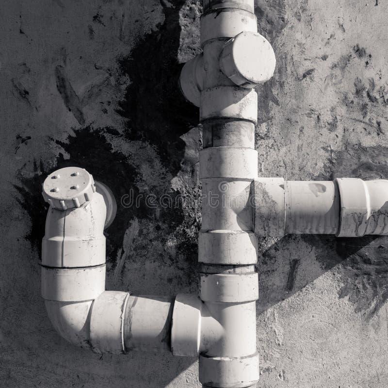 Tubos plásticos del drenaje en la pared blanca del indicador fotos de archivo