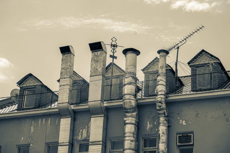 Tubos que fuman de aluminio de la ventilación y del calor fuera del edificio industrial viejo Blanco y negro, vintage de la sepia fotos de archivo