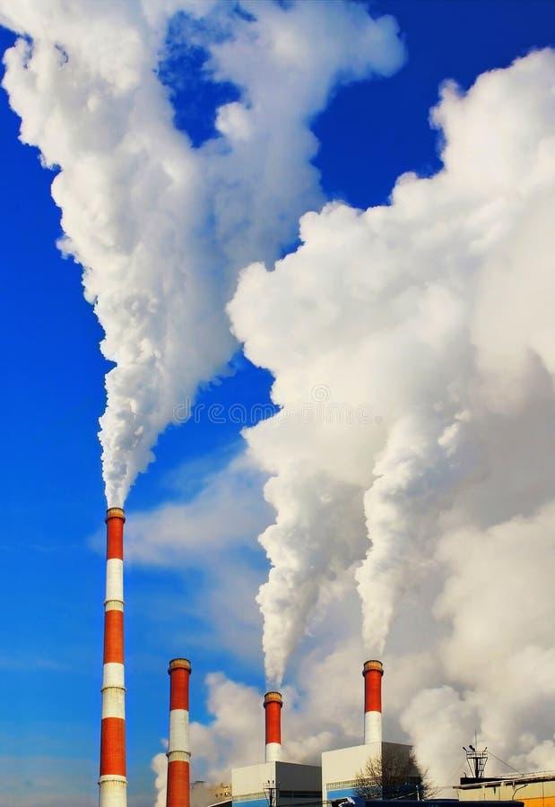 Tubos que fuman de la central térmico contra el cielo azul imagen de archivo libre de regalías