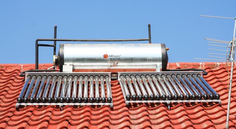 Tubos solares de la calefacción por agua en un tejado foto de archivo