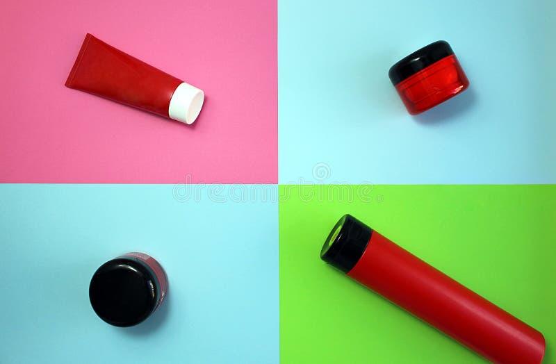 Tubos vermelhos para cuidados com a pele do corpo em um fundo colorido fotos de stock royalty free