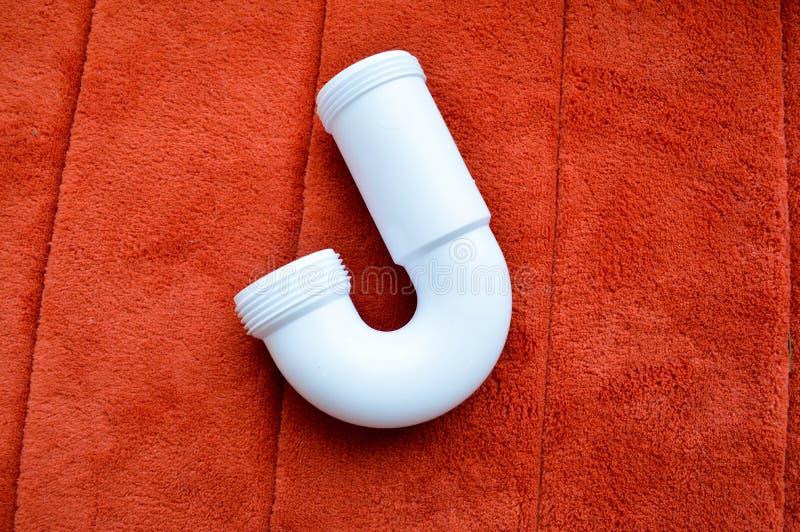 Tubulação curvada plástica branca em um tapete vermelho, fundo foto de stock royalty free