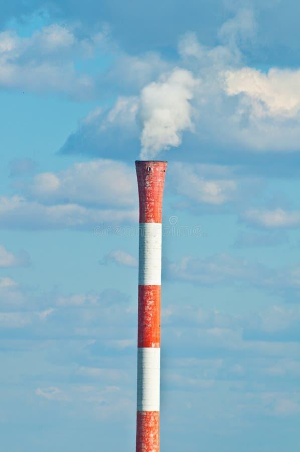 Tubulação da fábrica que fuma de encontro ao céu azul foto de stock