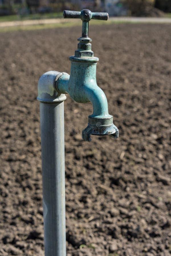 Tubulação de água velha, torneira com a torneira de água oxidada velha do fundo A da terra do marrom da natureza no jardim imagem de stock royalty free