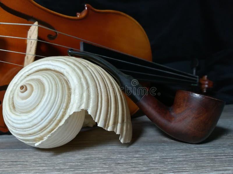A tubulação de cigarro, o violino velho e o mar vendem imagem de stock royalty free
